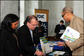 Congressional Affairs Specialist Arnold Cohen and Technical Assistant Courtney Cook offer materials, including OCC's Help With My Bank booklet, for a National Consumer Protection Week attendee.