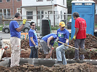 OCC employees Ammar Askari (left), Juan Marroquin (second from left), and David Permut (fourth from left) work with two other volunteers on the foundation of a home at the 2012 NeighborWorks Week site.